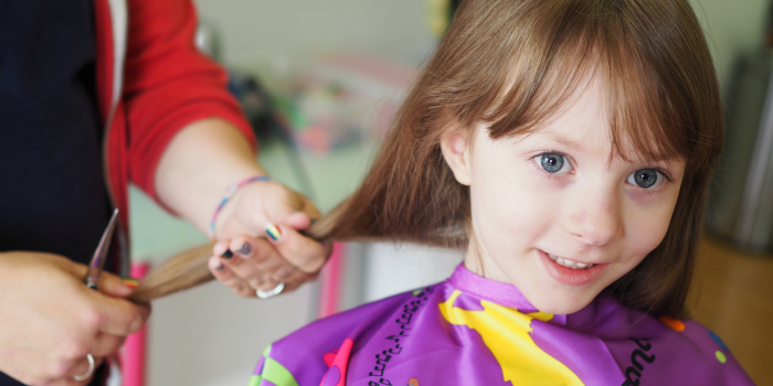 young girl having her pony tail cut off at hair salon