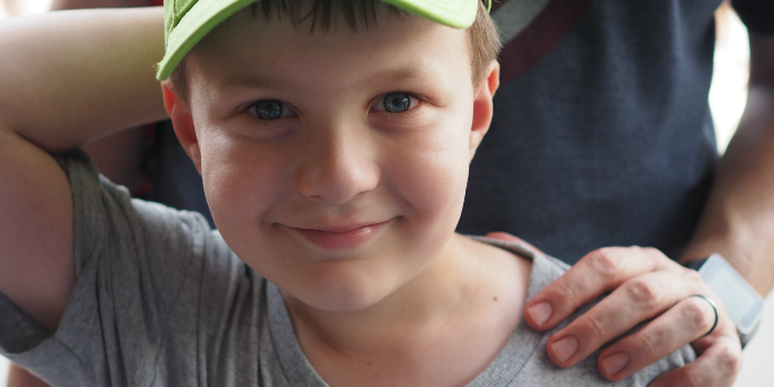 Young boy with a Monster's Inc cap wearing a first visit button at Walt Disney World's Magic Kingdom